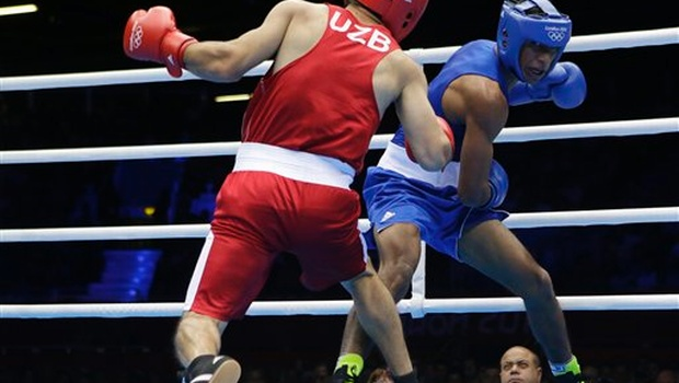 Uzbekistan's Abbos Atoev fights Morocco's Badr-Eddine Haddioui, right, during a middle weight 75-kg preliminary boxing match at the 2012 Summer Olympics in London. AP