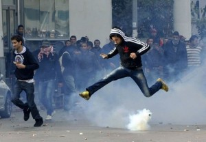 A Tunisian jumps over a tear gas canister fired by police outside the Interior Ministry during a protest over the killing of opposition leader and outspoken government critic Chokri Belaid, February 6, 2013 in Tunis.