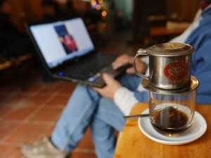 Image taken on January 15, 2013 shows a man reading the news on his laptop at a coffee shop in Hanoi, Vietnam (AFP-File, Hoang Dinh Nam)