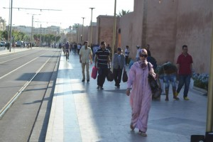 People walking near the Grand old wall in Rabat Medina. Photo by Morocco World News