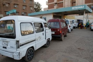 Drivers queue up in their vans for fuel at a gas station in the Sudanese capital Khartoum on December 21, 2013 (AFP, Ashraf Shazly)