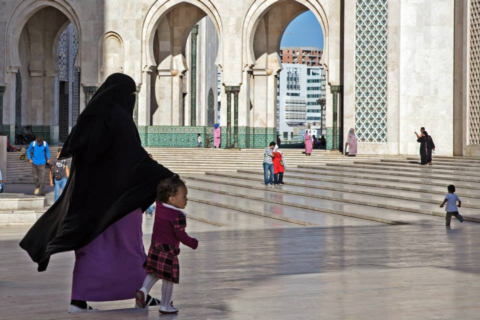 Moroccan Woman walking bear the Grand Mosque Hassan II in Casablanca