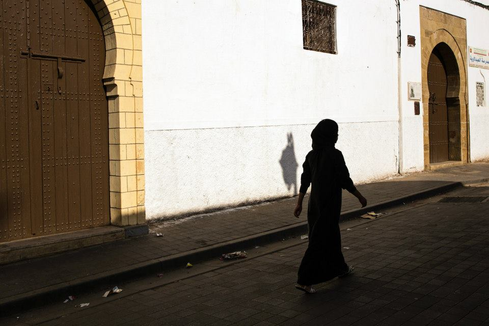 Moroccan Woman walking near a mosque in Casablanca