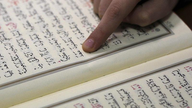 A young girl studies the Koran at a mosque in Dortmund, October 3, 2010. German President Christian Wulff used part of a speech celebrating two decades of democratic unity on Sunday to stress that Islam has a place in Germany.