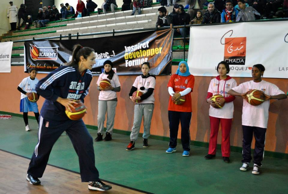 Ruth Riley, a forward:center with the Atlanta Dream, demonstrates basketball passing techniques to Moroccan girls in Azrou.