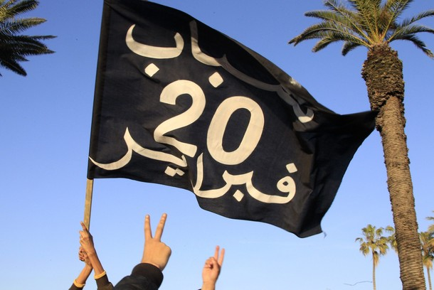 Demonstrators gesture as they hold a flag symbolizing the February 20th protest movement during a demonstration in Rabat
