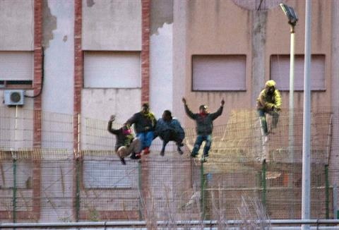 Immigrants scale over a border fence separating Spain'