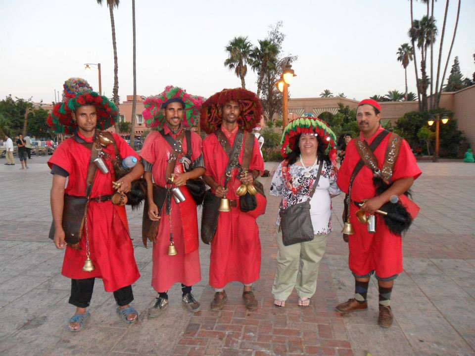 men dressed in red offering water. photo by Marisa Fernandez (Morocco World News)