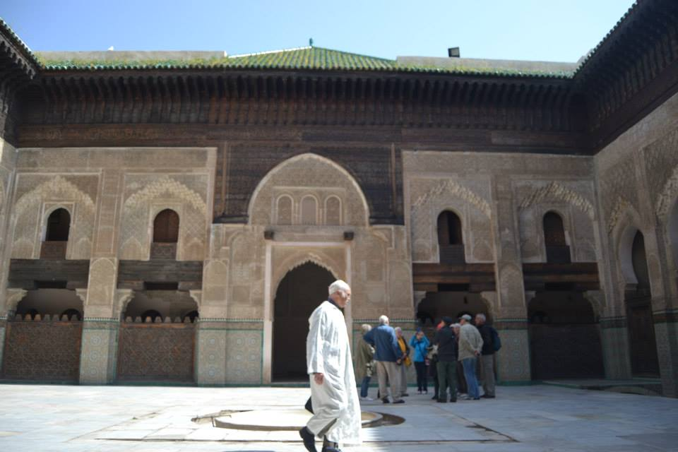 Moroccan Men walks by the Mederssa Bou Inania in Fez Medina. Photo by Morocco World News
