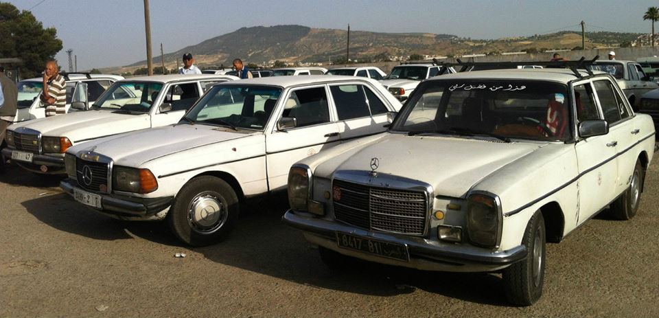 Grand taxis lined up in a row. Photo by Liz Yaslik
