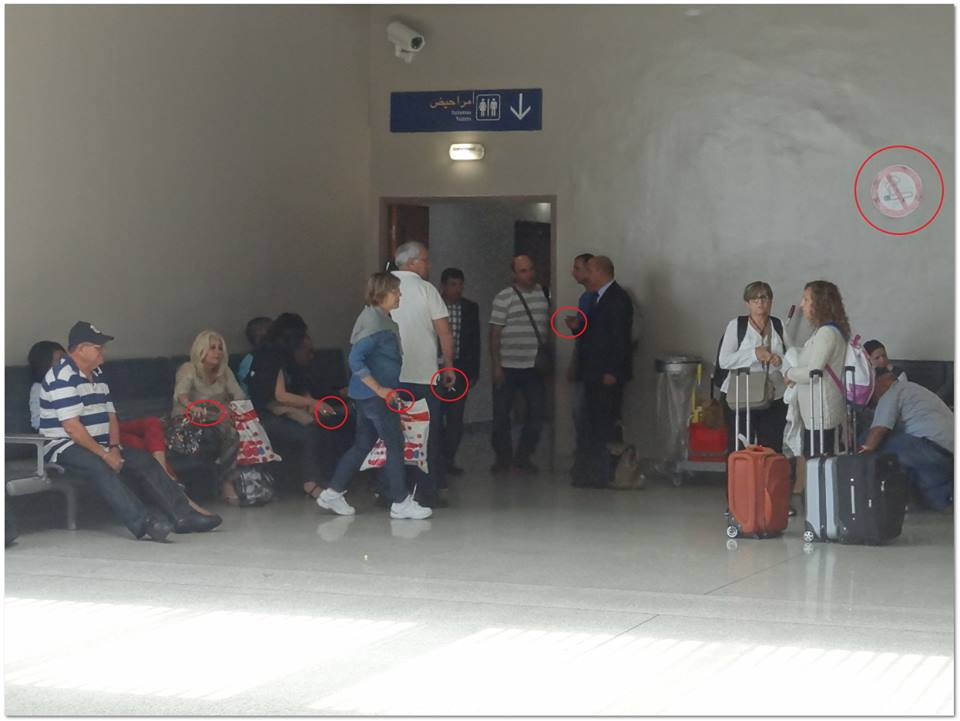 People smoking in Mohammed V Airport near a sign that says 'NO SMOKING'