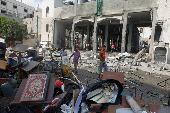 Palestinian boys walk past debris, including Korans and other items from a mosque destroyed in an overnight Israeli military strike, on July 22, 2014, in Rafah the southern Gaza Strip. (AFP Photo : Said Khatib)