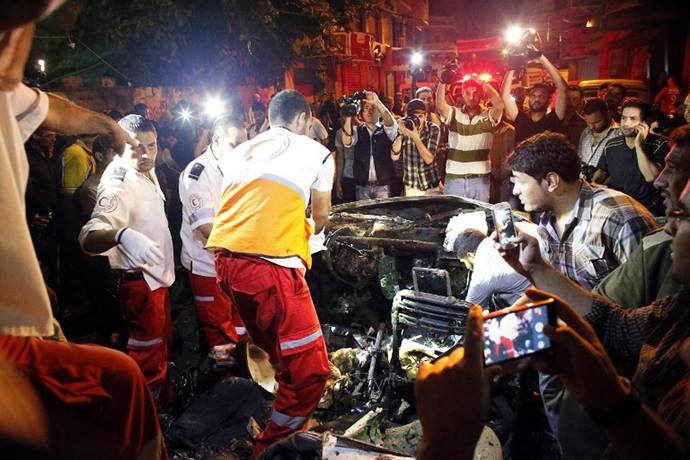 Palestinian rescuers check a car hit by an Israeli air strike killing the driver in Gaza City on July 9, 2014. (AFP Photo : Thomas Coex)