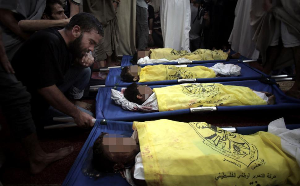 Palestinians mourn over thebodies of four boys from the same extended family in the mosque during their funeral in Gaza City on Wednesday. KHALIL HAMRA/AP