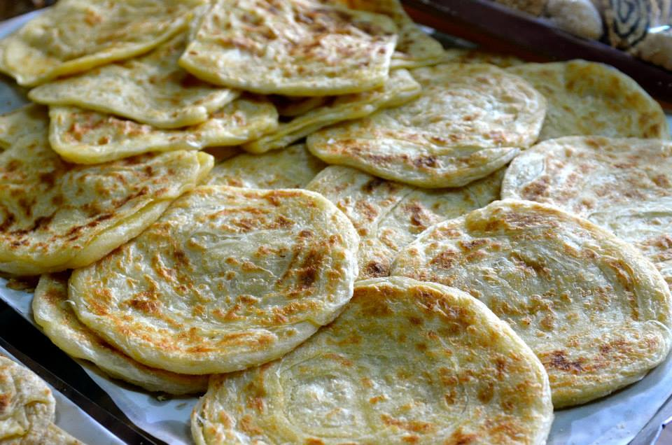 Is a squared crepe made of flat portions of dough that are fried in a pan producing a layered bread that is crispy on the outside and chewy on the inside.