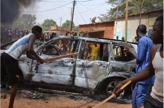 People hold wooden sticks next to a damaged car during a demonstration against French weekly Charlie Hebdo's publication of a cartoon of the Prophet Mohammed in Niamey, on January 17, 2015 ©Boureima Hama (AFP)