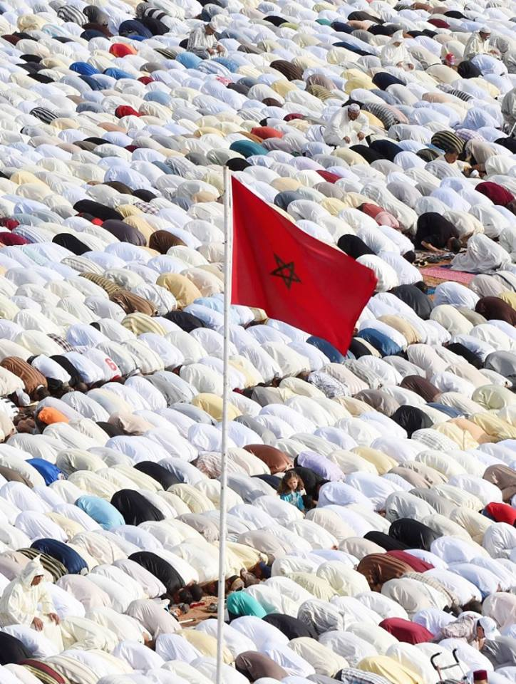 Worshippers in prostration position and Moroccan flag flies in the air