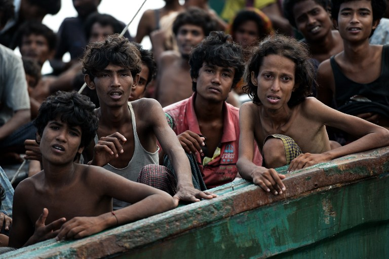 Rohingya migrants sit on a boat drifting in Thai waters off the southern island of Koh Lipe in the Andaman sea on May 14, 2015. The boat crammed with scores of Rohingya migrants -- including many young children -- was found drifting in Thai waters on May 14, according to an AFP reporter at the scene, with passengers saying several people had died over the last few days. AFP PHOTO / Christophe ARCHAMBAULT
