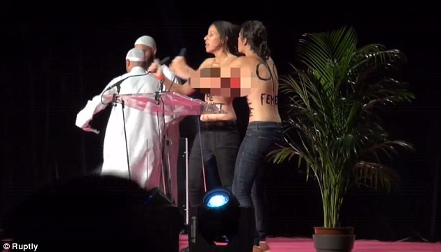 The two activists grabbed the microphones and punched in the air as the two imams retreated to the back of the stage.