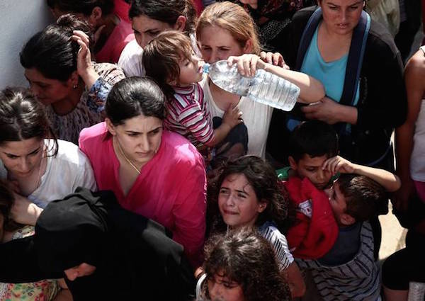 A girl cries as hundreds of migrants gather for a registration procedure at the stadium of Kos town, on the southeastern island of Kos, Greece, Tuesday, Aug. 11, 2015.