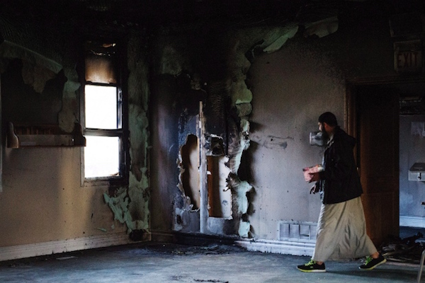 Imam Shazim Khan walks past a charred wall on Sunday as he cleans up after the fire. The blaze, which was set intentionally, caused more than $80,000 in damage. (Christopher Katsarov:Canadian Press)