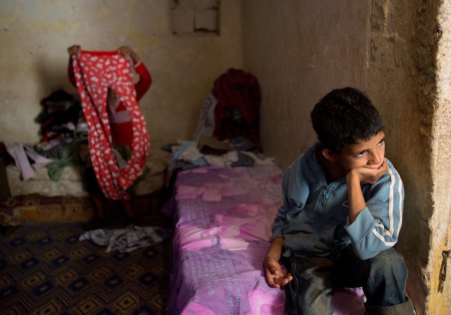 "Abdelaziz, 10, sits and looks into the kitchen while his mother, Aziza Mohammed Kanzi, 39, folds clothes behind him. Kanzi's 4 illegitimate children live with her in a small shack in the slums of Sahb Al Caid in Salé. ""[My children] will blame me for this poor life conditions,"" Kanzi said."