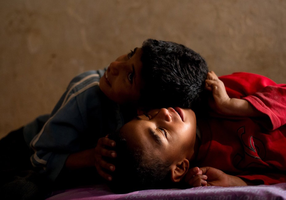 From left, Abdelaziz & Sifeddine, 6, wrestle each other on a cushion in their shack. Kanzi describes her children like a gang, or a footbal team.