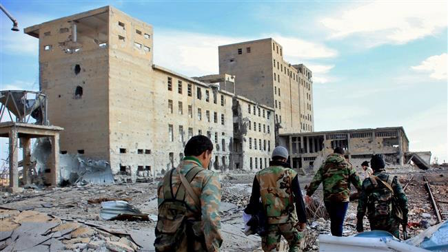 Syrian army soldiers patrol near a building in the countryside of Deir Hafer, near the northern Syrian city of Aleppo on December 2, 2015. (AFP photo)