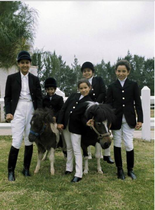 KIng Mohammed VI when he wa a little boy with his relatives posing for a picture with poneys