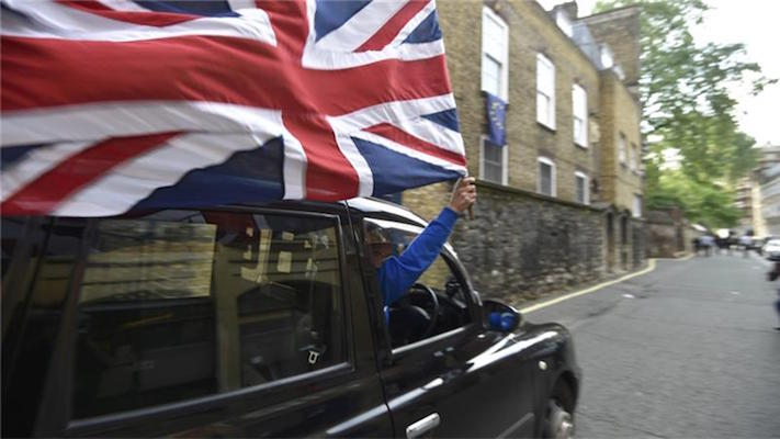 A taxi driver holds a Union flag, celebrating the result of the vote [Toby Melville:Reuters]