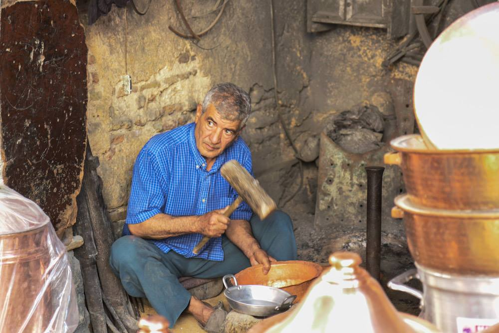 Moroccan Craftsman hammering a metal fixture in Saffarine square