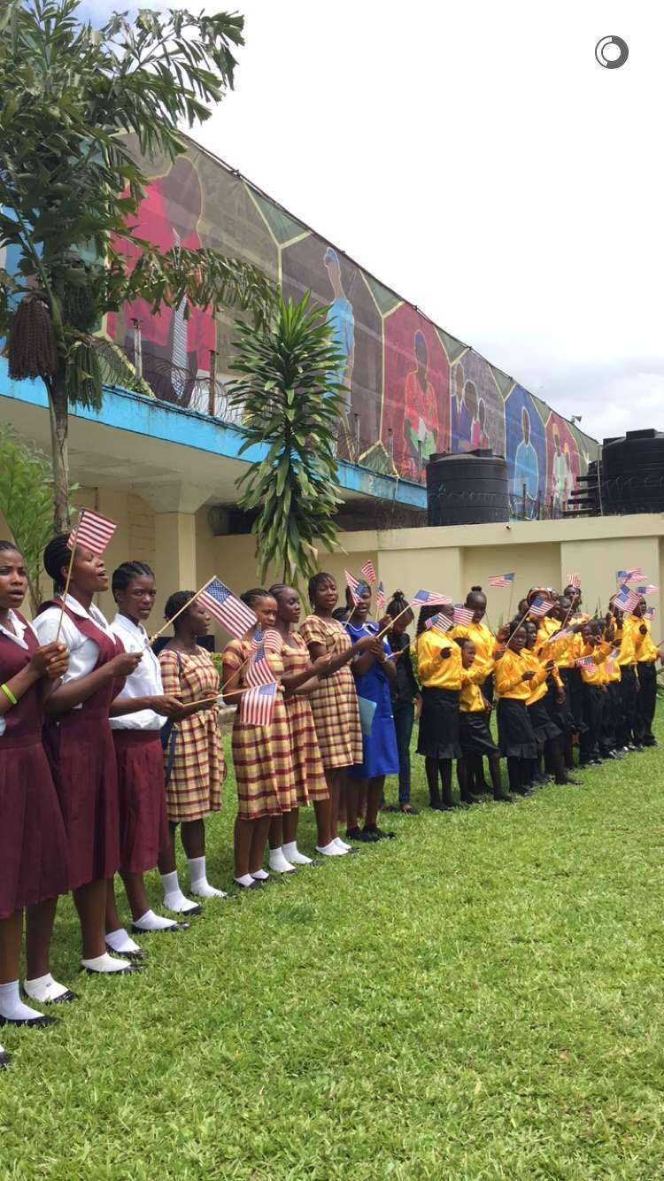 Mrs. Obama sitting with a Liberian woman and meeting Liberian schoolchildren