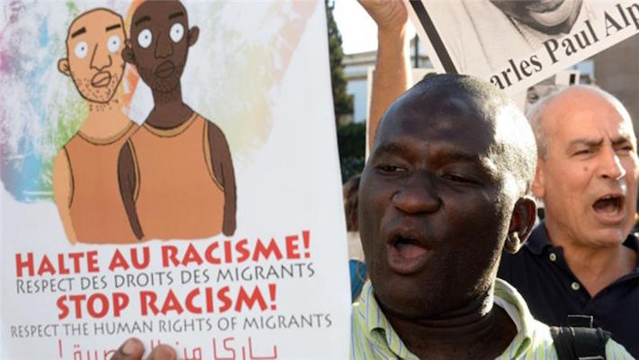 Protesters shout slogans as they hold placards during a demonstration in Rabat against racism in