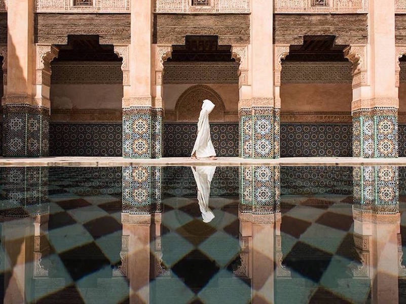 A shot of a hooded man in the Ben Youssef Madrasa in Marrakech
