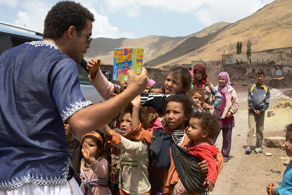 Man handing out books to young Moroccan girls in the Atlas Mountains
