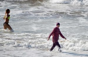 """A Moroccan woman wearing a """"burkini"""" (C), a full-body swimsuit designed for Muslim women, enters the sea at Oued Charrat beach, near the capital Rabat, on August 17, 2016. (AFP Photo / Fadel Senna)"""