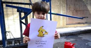 A boy holds up a photo of a Pokémon CREDIT: REVOLUTIONARY FORCES OF SYRIA MEDIA OFFICE