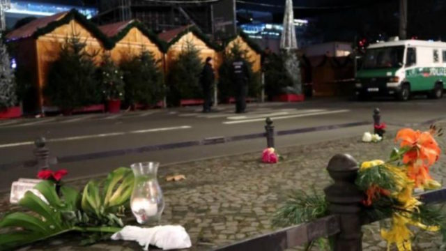 A candle and flowers are seen near the site where a truck ploughed through a crowd at a Berlin Christmas market in west Berlin.