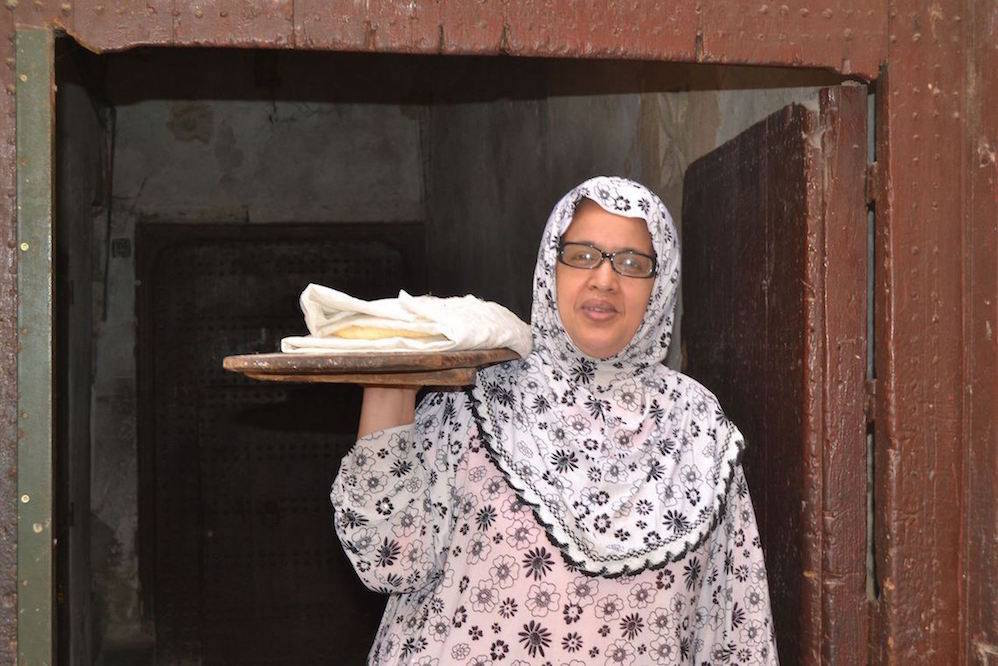 Local woman takes her freshly made bread to the nearby bakery in Fez Medina