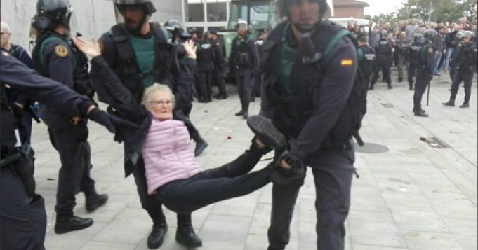 Elderly protester seen helpless as she is lifted up from the ground by two policemen.