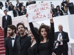 "ADDS IDS - Lebanese actress Manal Issa, from ""My Favorite Fabric,"" right, holds a sign that reads ""Stop the Attack on Gaza"" at the premiere of the film ""Solo: A Star Wars Story"" at the 71st international film festival, Cannes, southern France, Tuesday, May 15, 2018. Israeli soldiers shot and killed 59 Palestinians and wounded hundreds in mass protests on the Gaza border on Monday. Also with Issa are filmmakers Etienne Kallos, second left, and Gaya Jiji, second right. ("