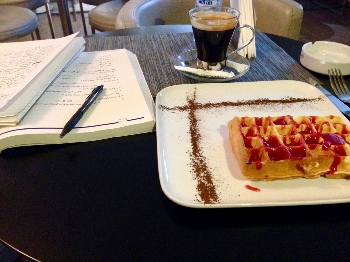 Moroccan cafe with waffle and coffee and Arabic homework.