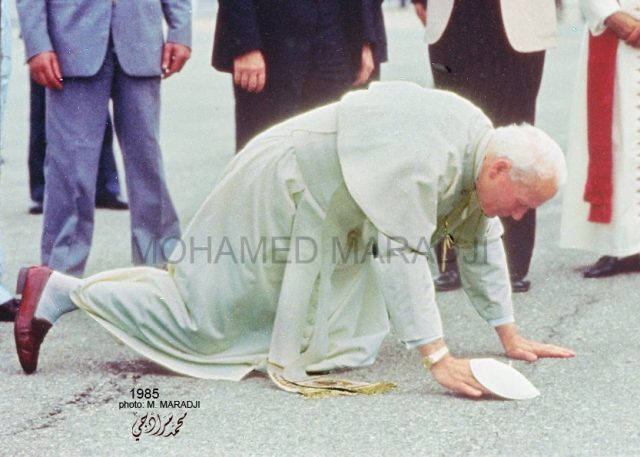 Pope John Paul kneeling to kiss Moroccan soil. August, 1985.