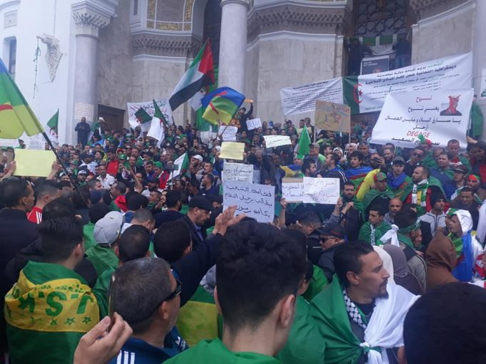 protesters carrying flags in Algeria