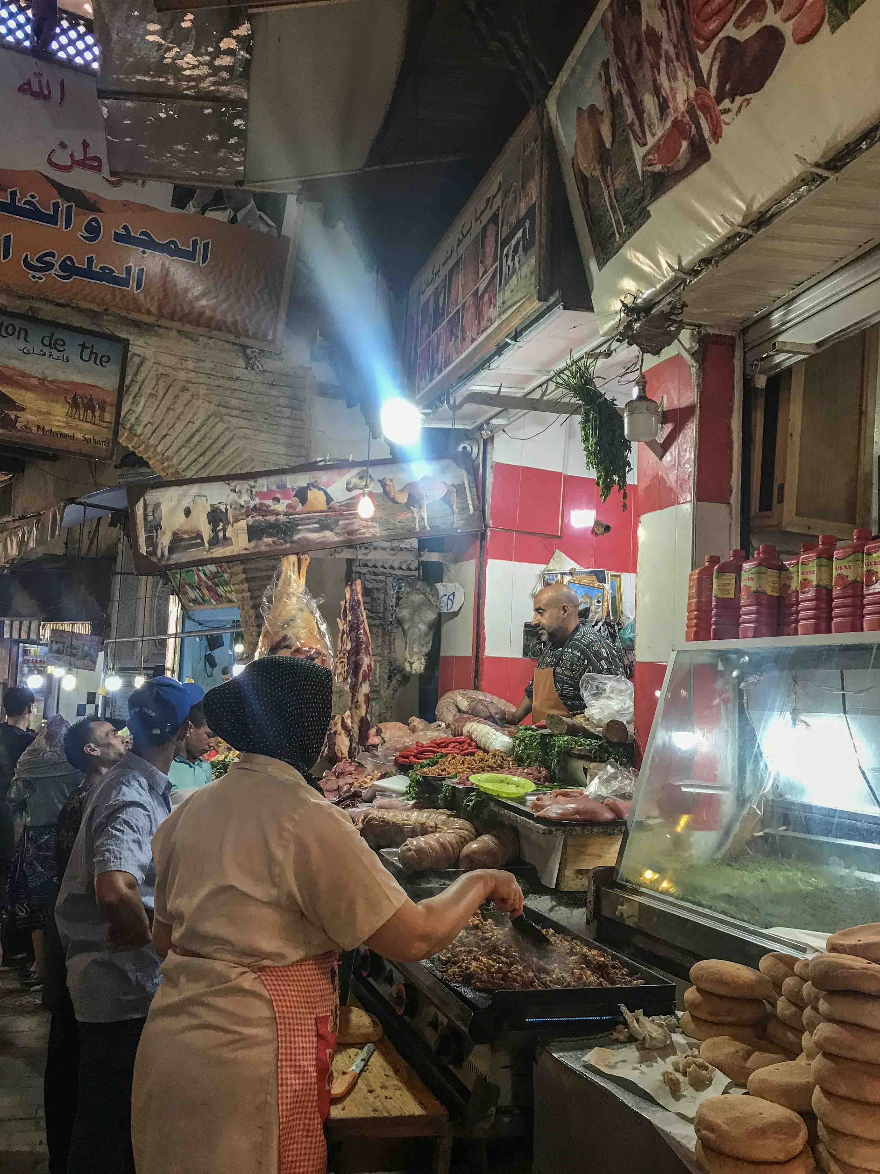 View on one street within the medina - the stand to the right sells camel meat and even has a camel head on display.