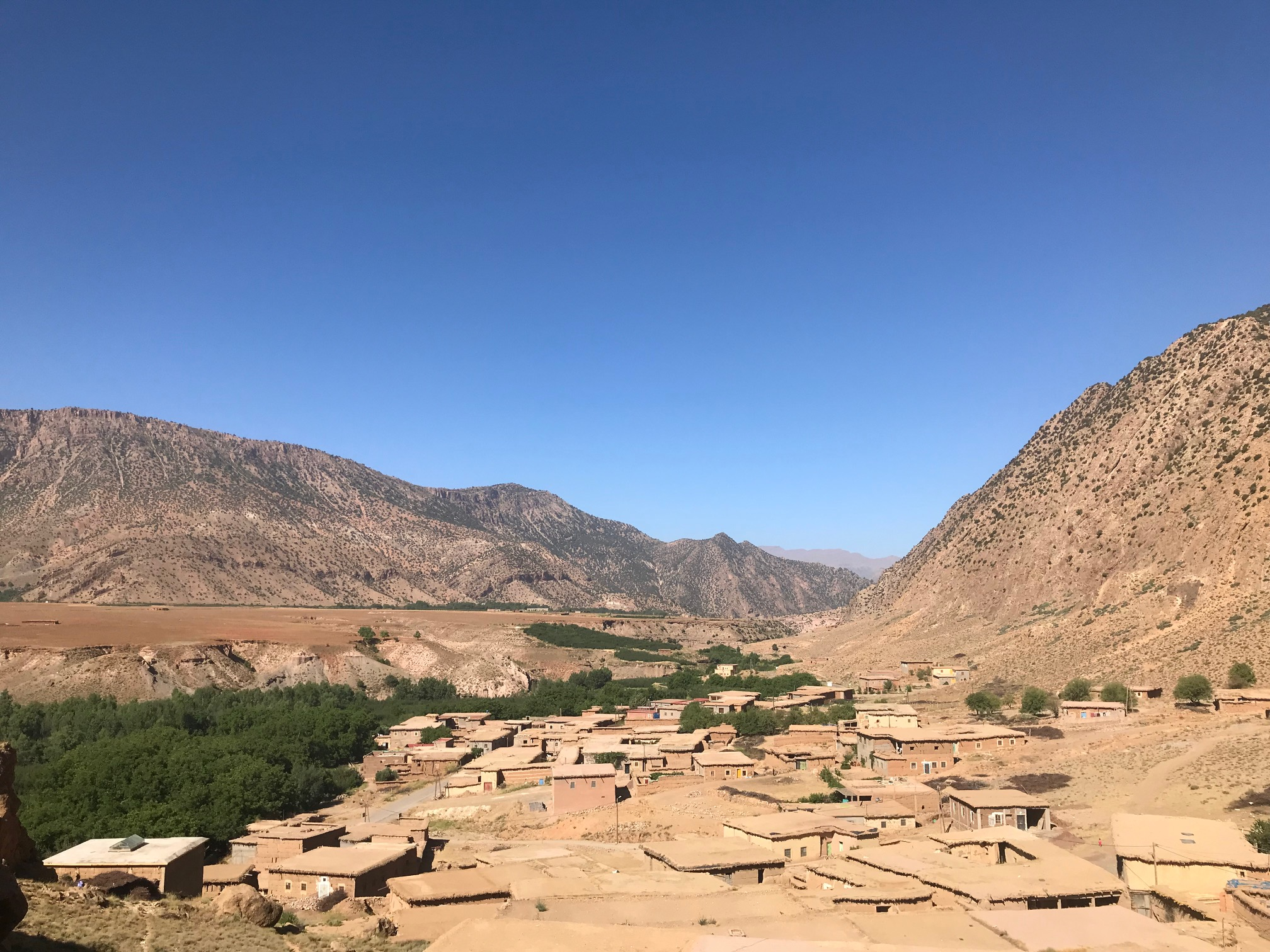 The mud brick houses form a patchwork of square brown roofs near the river.