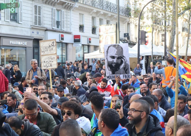 Protesters marching through the streets of Paris, showing a picture of Mohcine Fikri